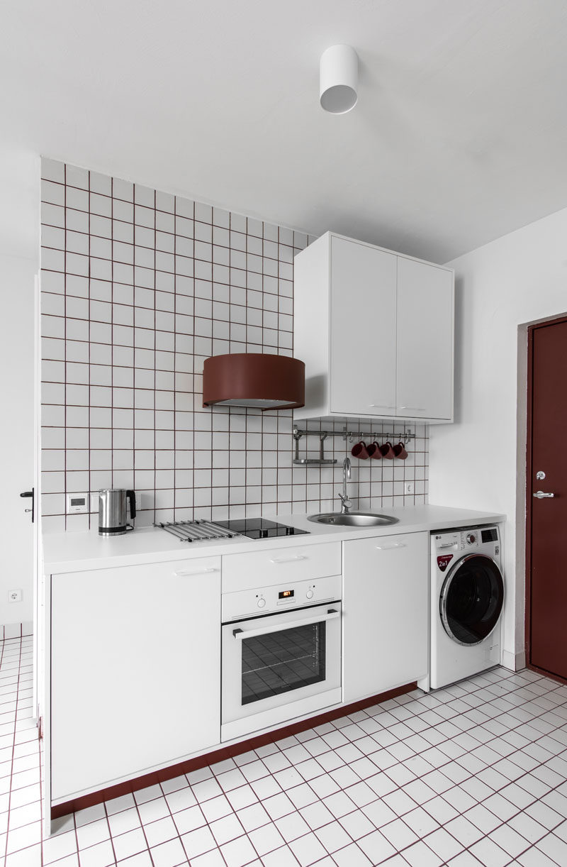 This small and white kitchenette uses red grout to add a pop of color. #Kitchenette #ModernKitchen #SmallKitchen #RedGrout