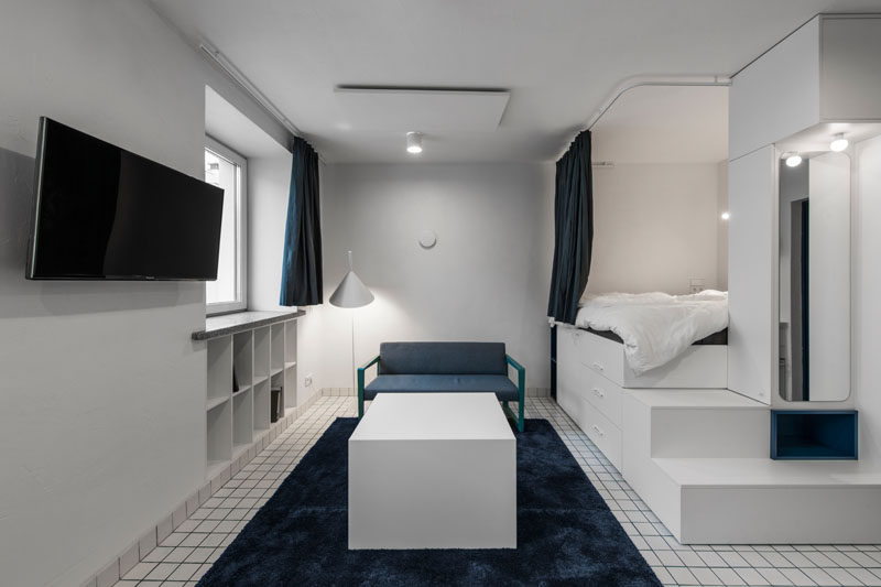 This modern micro apartment has a lofted bed with storage underneath, a living area, kitchenette, and bathroom. #MicroApartment #StudioApartment #LoftBed #BedWithStorage #SmallApartment #BlueGrout