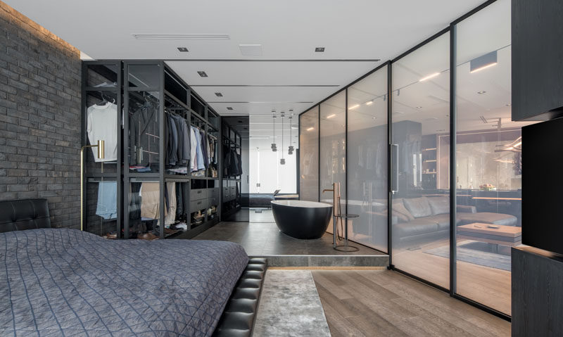 This modern bedroom features a 'smart glass' wall that transforms from transparent to opaque, and a movable wardrobe that expands to allow access to all of the clothes. #SmartGlass #GlassWall #InteriorDesign