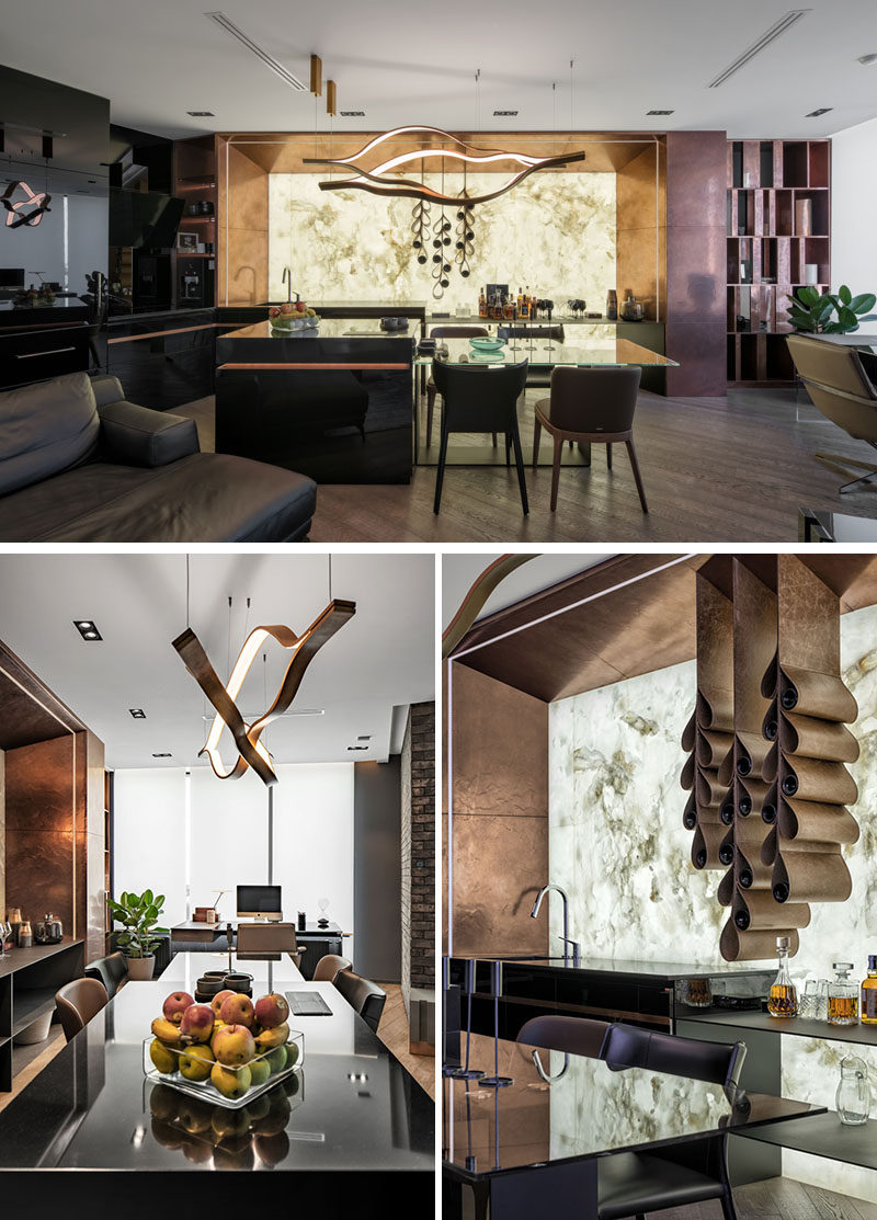 In order to add a touch of brightness to this modern apartment,a panel of backlit white onyx framed by copper edging, is featured in the kitchen. #BacklitOnyx #Onyx #ModernKitchen #WineStorage #Copper