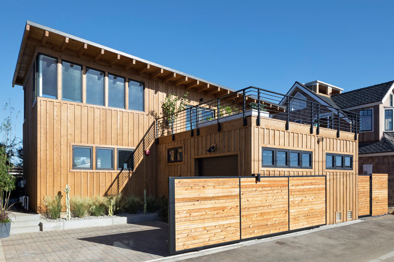 At the rear of this modern house is the garage, with the rooftop of the garage becoming the deck located off the dining room. #Garage #ModernHouse #RooftopDeck