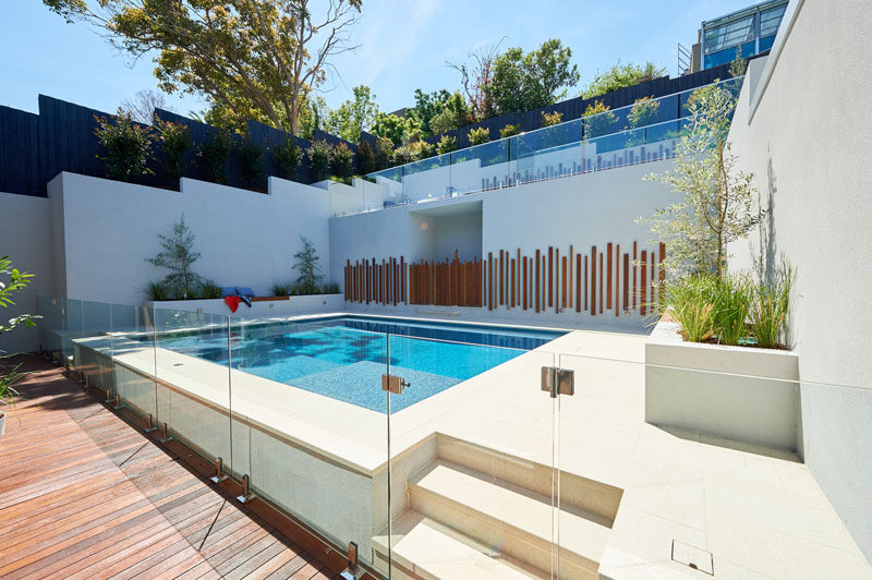 This modern backyard has a swimming pool, planter boxes with built-in seating, and an upper level with a curved lounge and grassy area. #Landscaping #ModernPool #PoolDesign #LandscapeDesign