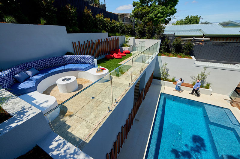 In this modern backyard, stairs lead from the pool level up to the lounge area with a built-in curved seating area, a touch of grass, and a glass railing that allows unobstructed views overlooking the pool and house. #ModernBackyard #LandscapeDesign #Garden #Pool #Landscaping