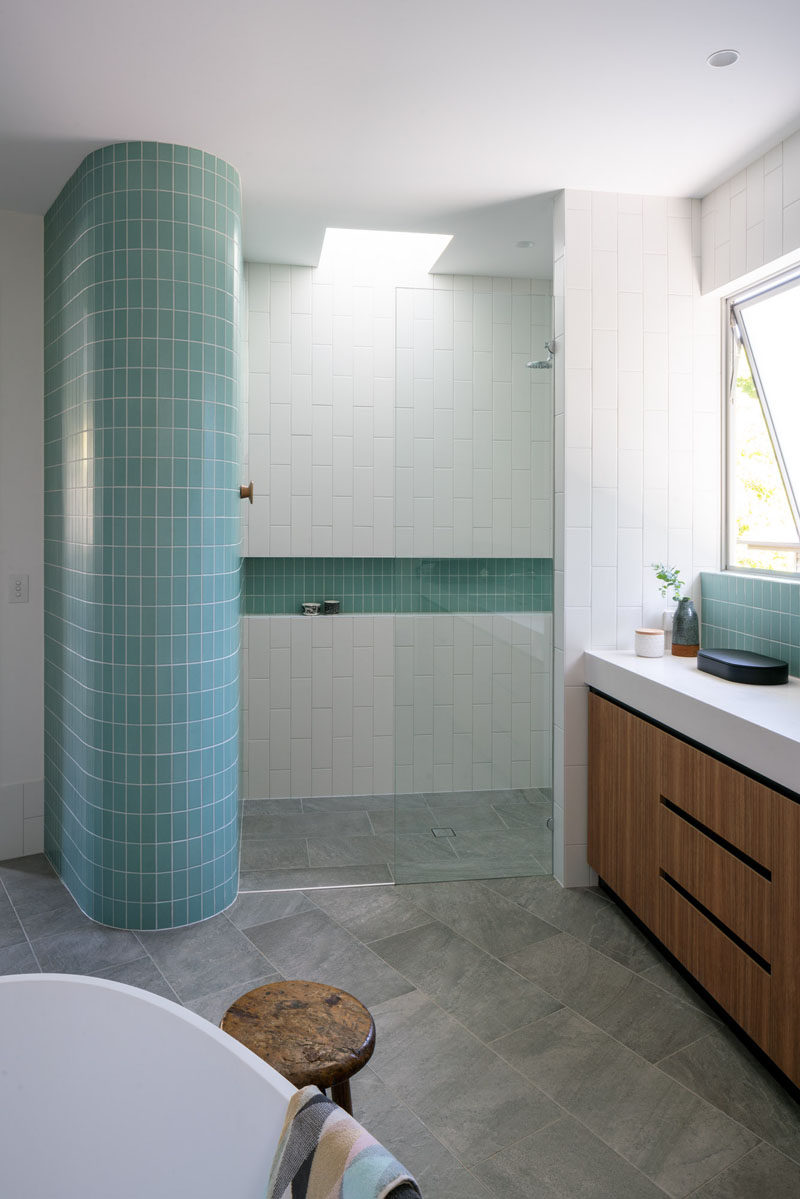 This modern bathroom features turquoise tiles that wrap around a curved wall, while white subway tiles have been laid vertically, drawing your eye upwards to the small skylight in the shower. #ModernBathroom #Tiles #Skylight #Shower