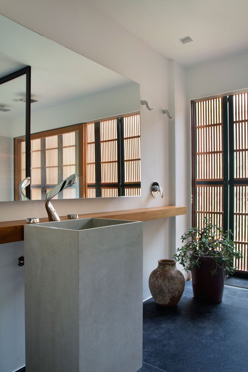 In this modern bathroom, a large mirror reflects the natural that comes through the wooden slat, while a sliding wood framed glass door can be opened to have a breeze flow through the room. #BathroomDesign #ModernBathroom