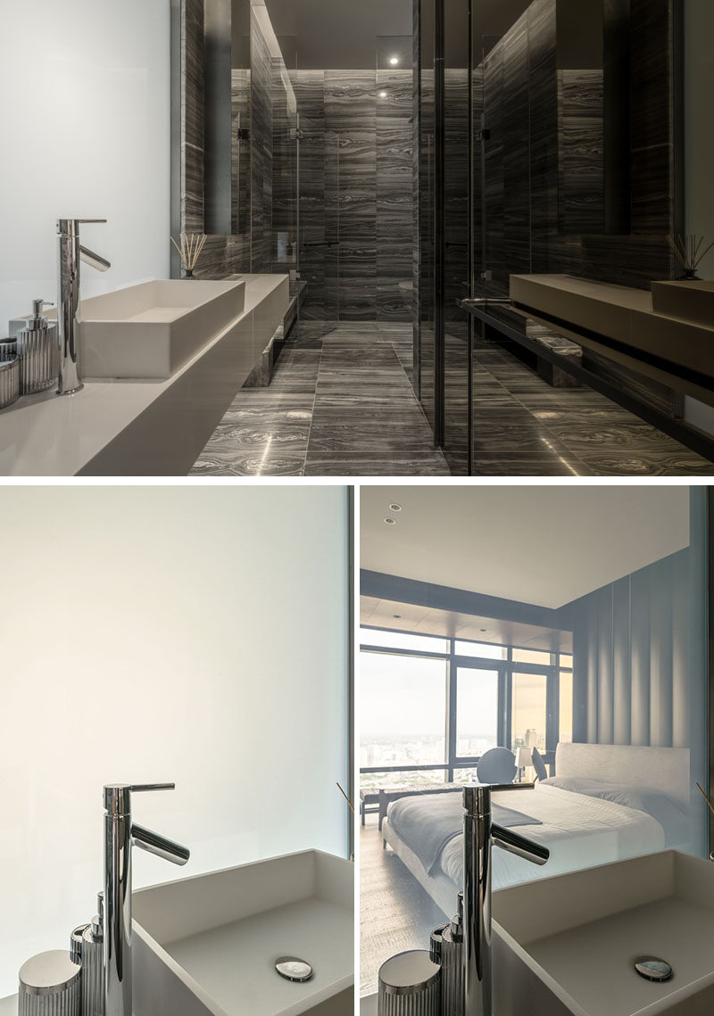 This modern bathroom uses natural stone on the floor and walls, while an opaque glass panel becomes transparent and provides a view of the bedroom. #ModernBathroom #BathroomDesign