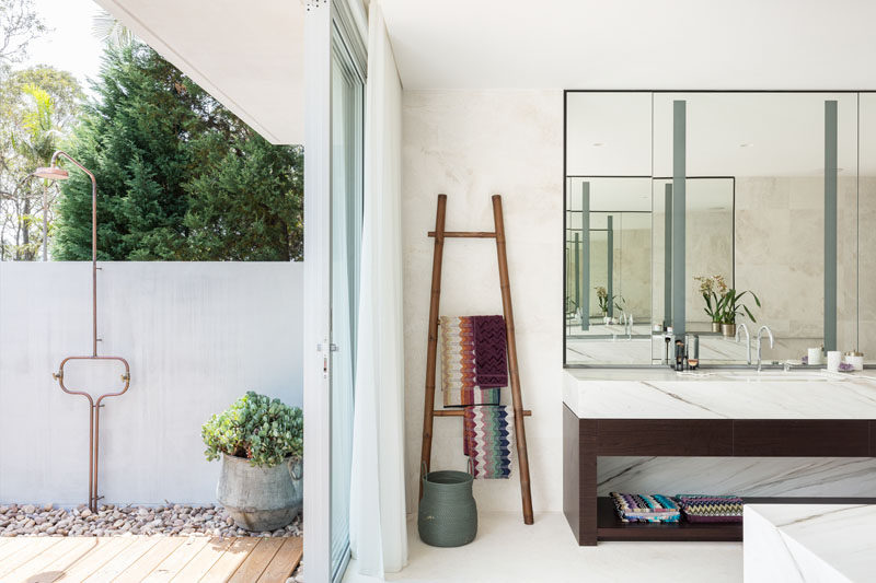 This moder master bathroom has a sliding glass door that opens to reveal an outdoor shower. #OutdoorShower #MasterBathroom #BathroomDesign