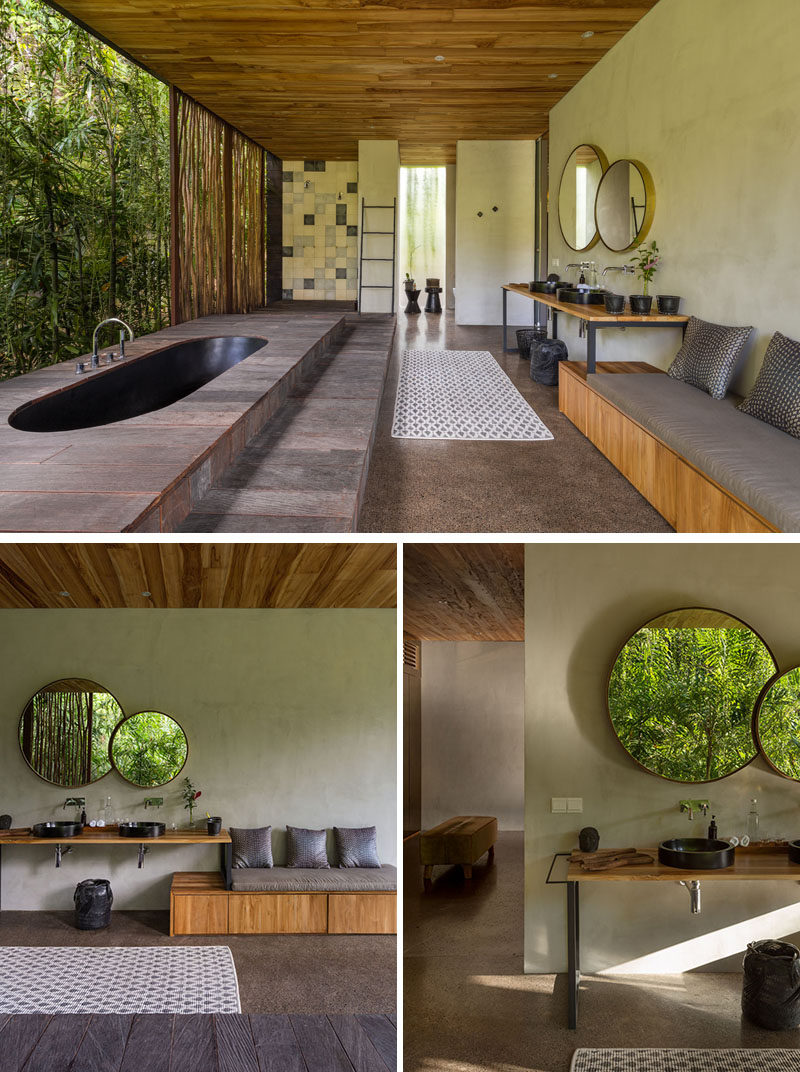 In this modern bathroom, a black sunken bathtub is positioned for relaxing tropical garden views.