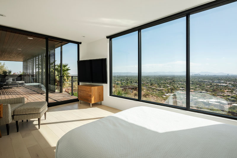 This modern bedroom opens up to a covered patio, while large picture windows perfectly frame the view. #Windows #Bedroom