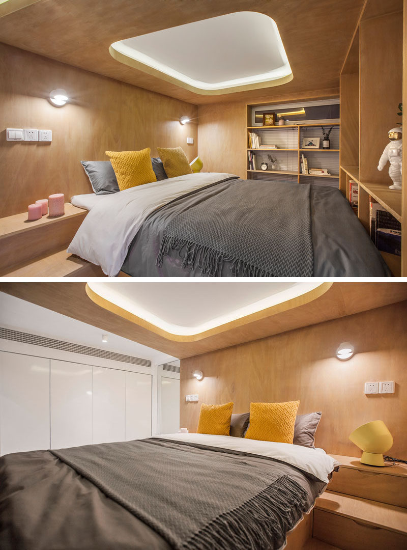 This small apartment makes use of the ceiling height to raise the bed up and place it within a wood box, and therefore allowing storage to be included under the bed and within the stairs. #Bedroom #RaisedBed #PlatformBed #BedroomDesign #ModernBedroom #SmallBedroom