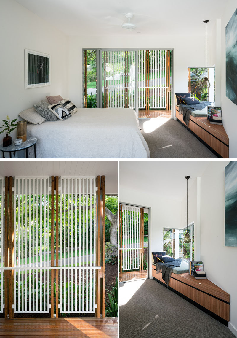In this contemporary master bedroom, there's a built-in window seat that makes use of the corner, while a sliding glass door opens up to a small outdoor space with a privacy screen. #WindowSeat #ModernBedroom #BedroomDesign