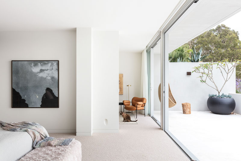 This modern master bedroom opens up to a private balcony that's decorated with a hanging chair and a large round black planter. #MasterBedroom #Balcony #SlidingGlassDoors