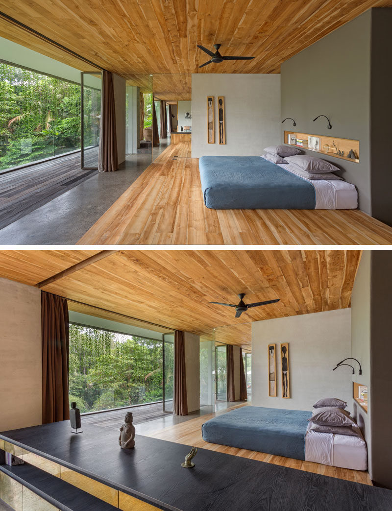In this modern bedroom, a grey colored wall with a built-in shelf becomes the headboard for the bed, while wood features heavily on the ceiling and on the floor. #ModernBedroom #WoodCeiling #WoodFloor