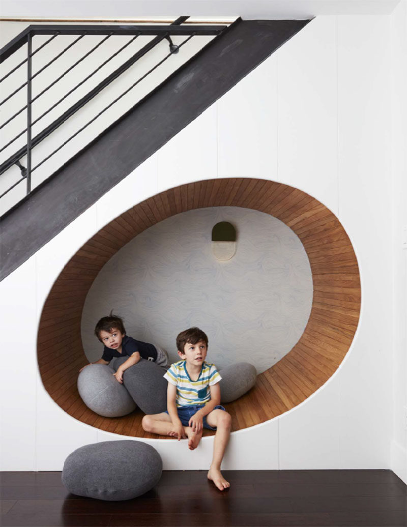 This contemporary townhouse has a wood-lined, built-in curved seating nook under the stairs. #SeatingNook #InteriorDesign