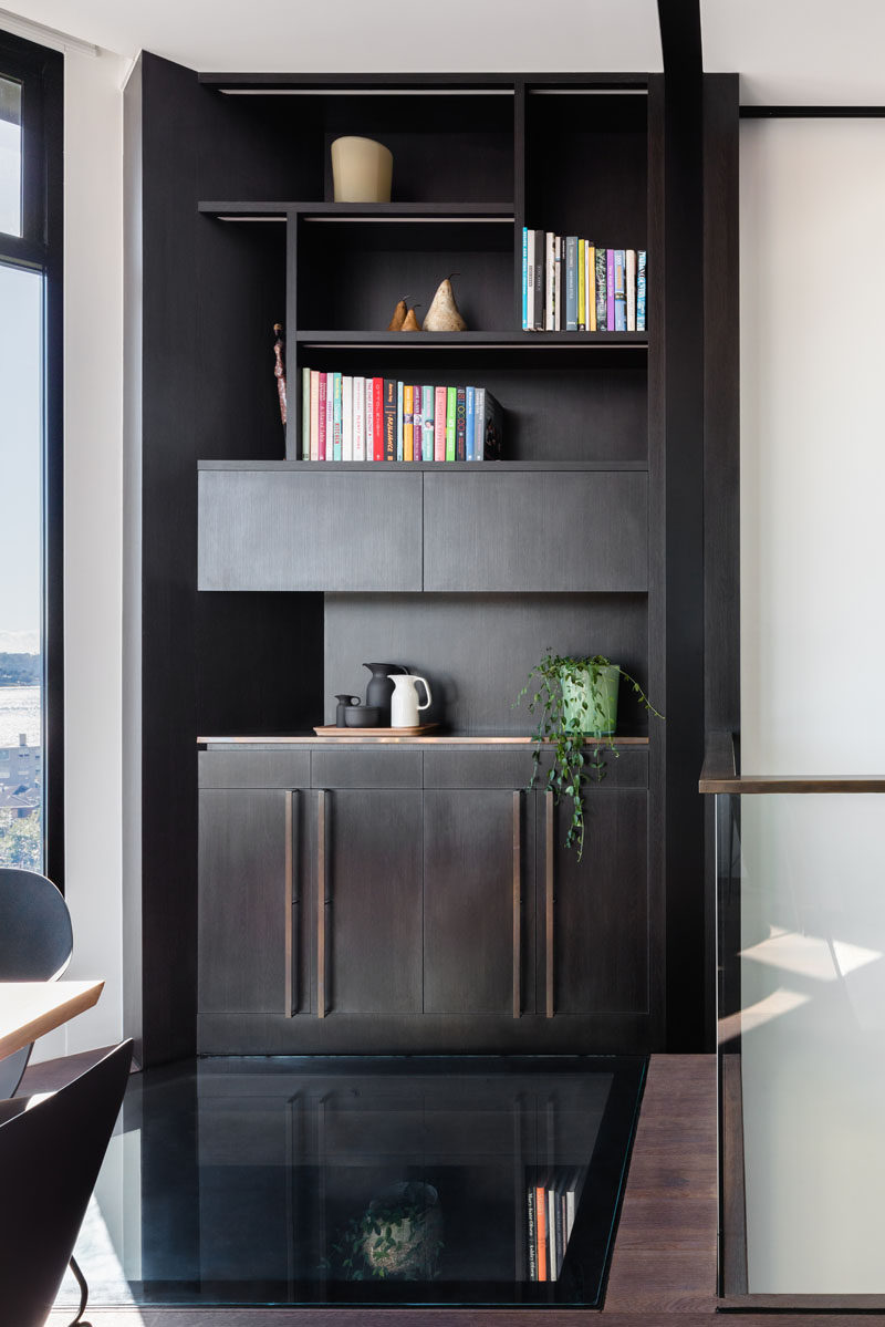 This modern home features a custom designed dark wood shelving unit, and on the floor is a glass section that lets light travel through to the level below. #GlassFloor #Shelving
