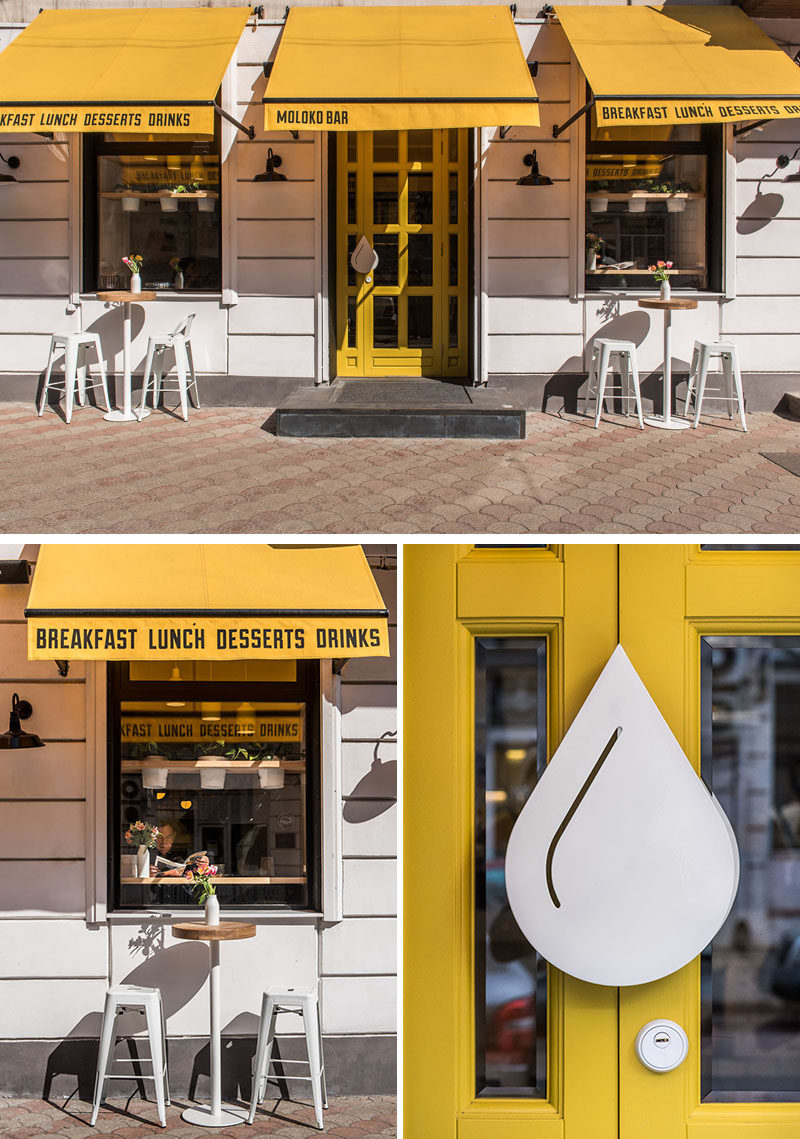 The bright white facade of this modern cafe is highlighted by the use of yellow awnings and a yellow door. #ModernCafeExterior #CafeDesign