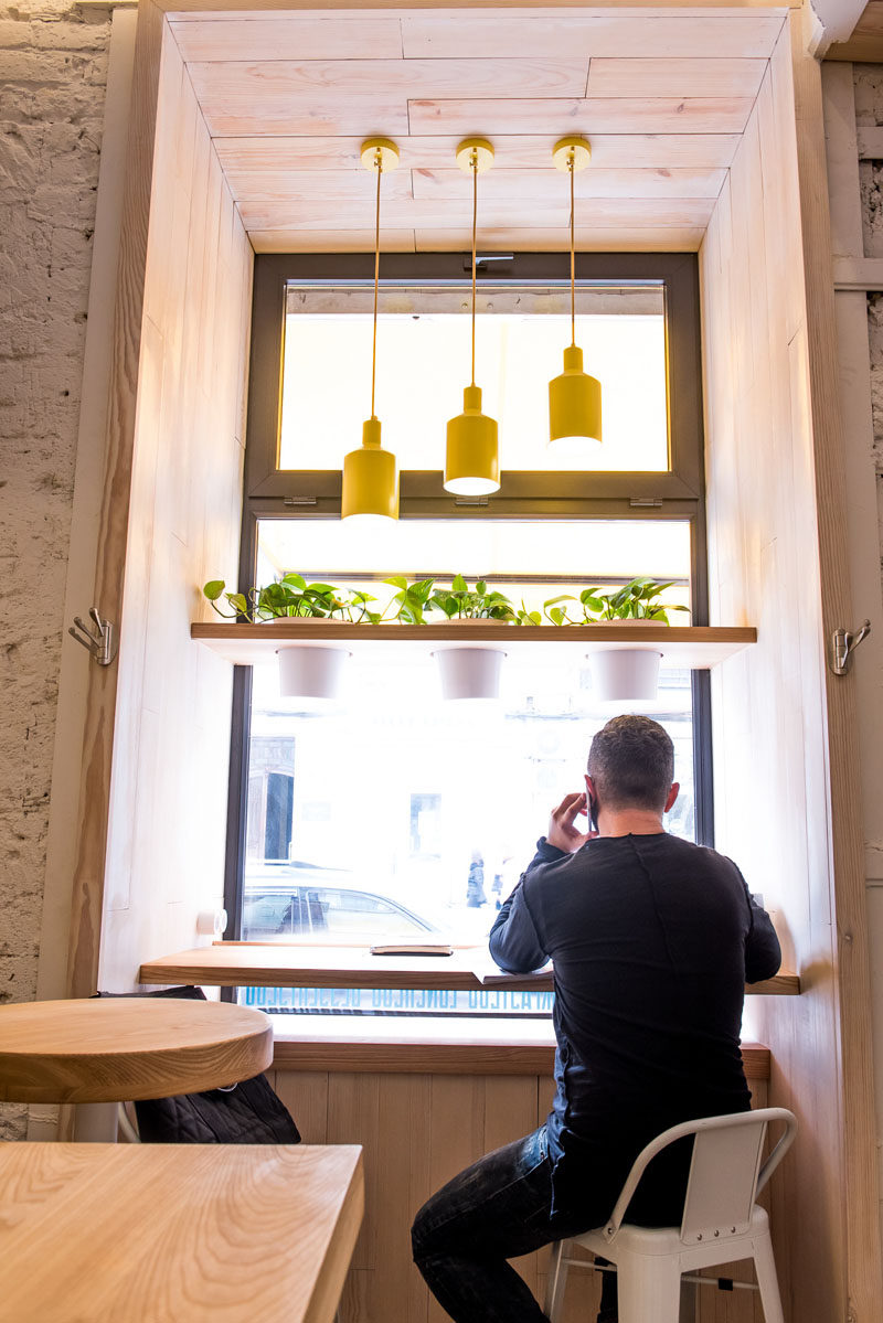 In this modern cafe, bar height counters and stools have been positioned in a window alcove looking out onto the street. #CafeDesign #CoffeeShop #InteriorDesign