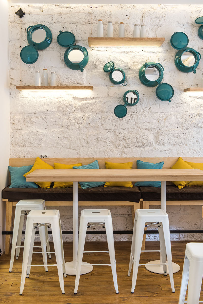 This modern cafe features a textured wall that's been decorated with painted portholes, floating wood shelves, and a long communal table with stools and seating. #ModernCafe #CafeDesign #Shelving #WallDecor