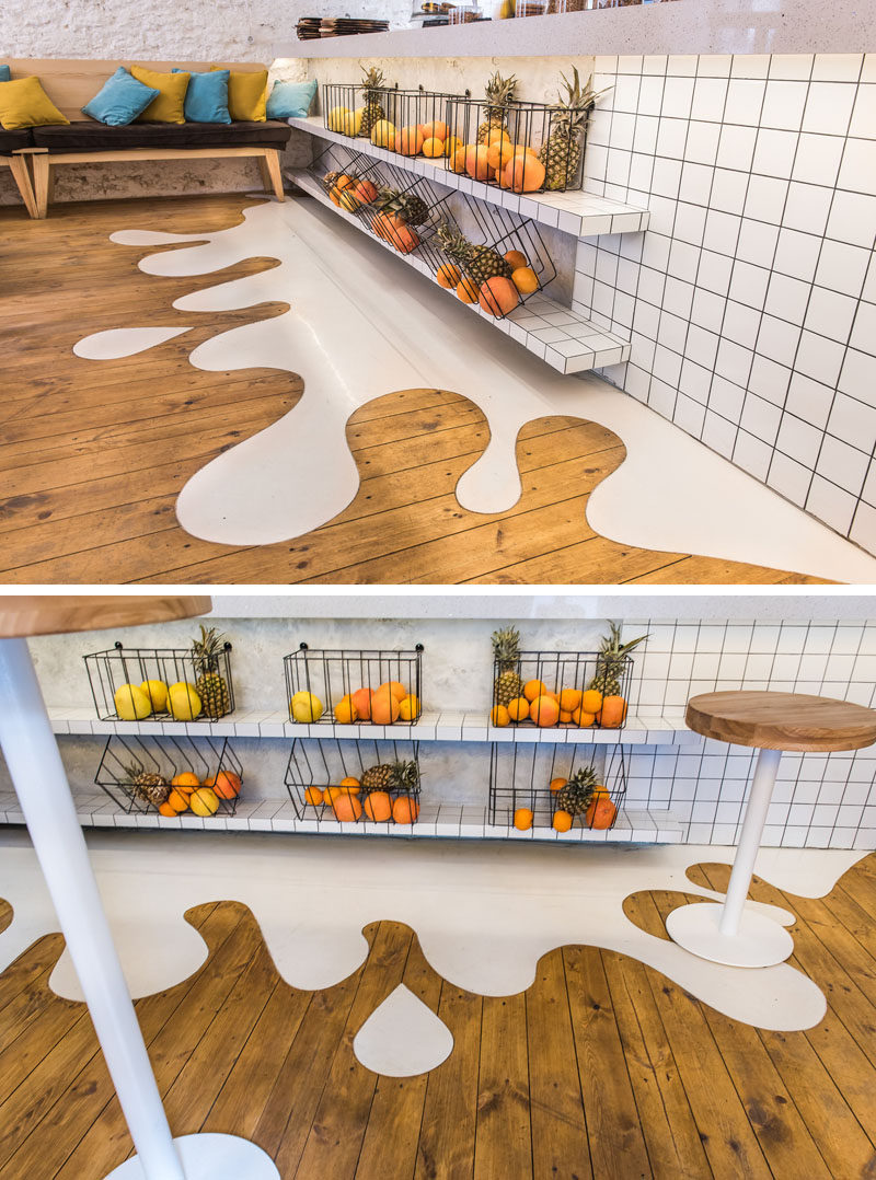 One of the fun elements in this modern cafe is a white 'splash' floor design that connects with the wood floor.  #Flooring #FunFlooring