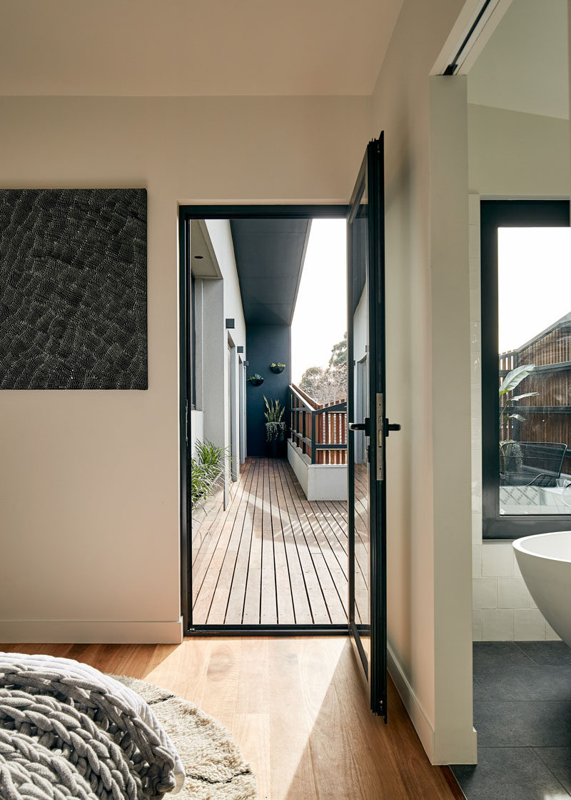 In this modern master bedroom, wood flooring has been used to add warmth to the room, and a glass door opens to a balcony. #Bedroom #WoodFloor #GlassDoor #Balcony