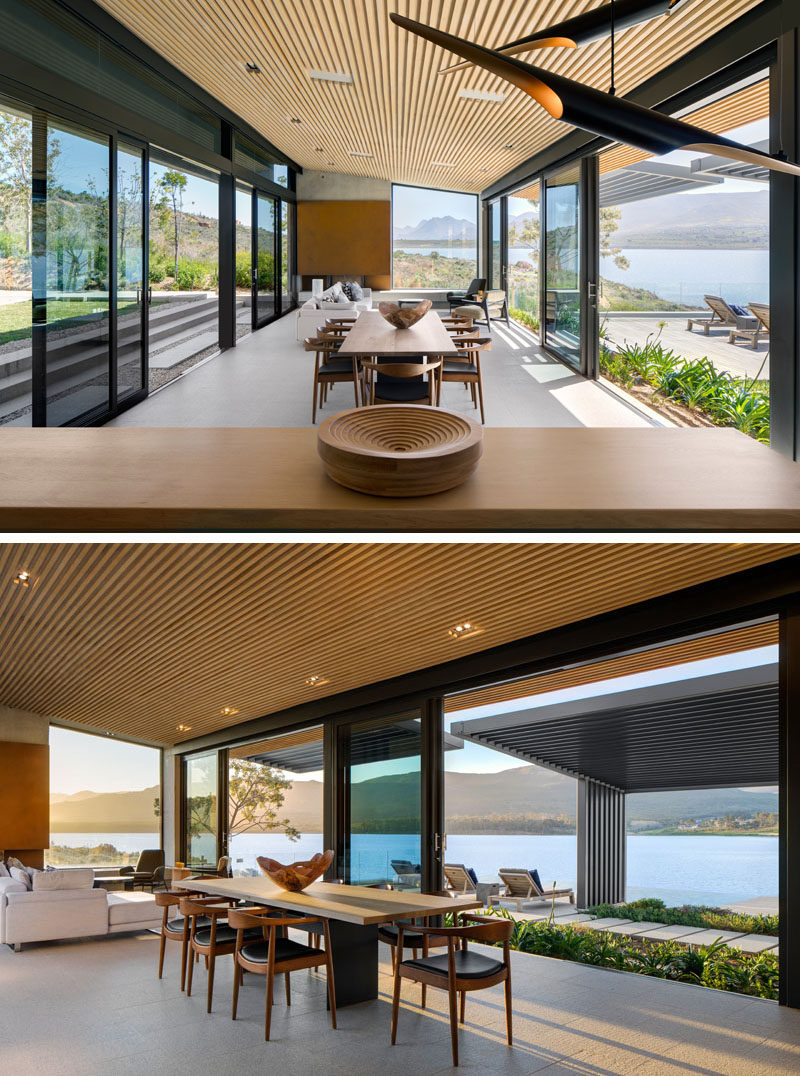 This modern open plan living and dining area opens to the outdoors on both side, while granite covers the floor and wood slats are featured on the ceiling. #DiningRoom #LivingRoom #OpenPlanInterior