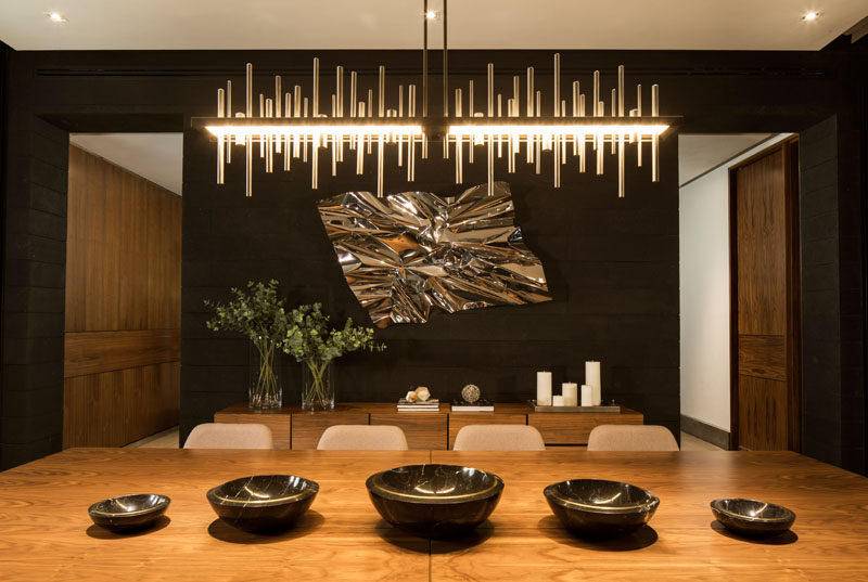 In this modern dining room, a sculptural chandelier brightens the room, while the light is reflected in the metallic wall sculpture. #DiningRoom #ModernDiningRoom #InteriorDesign
