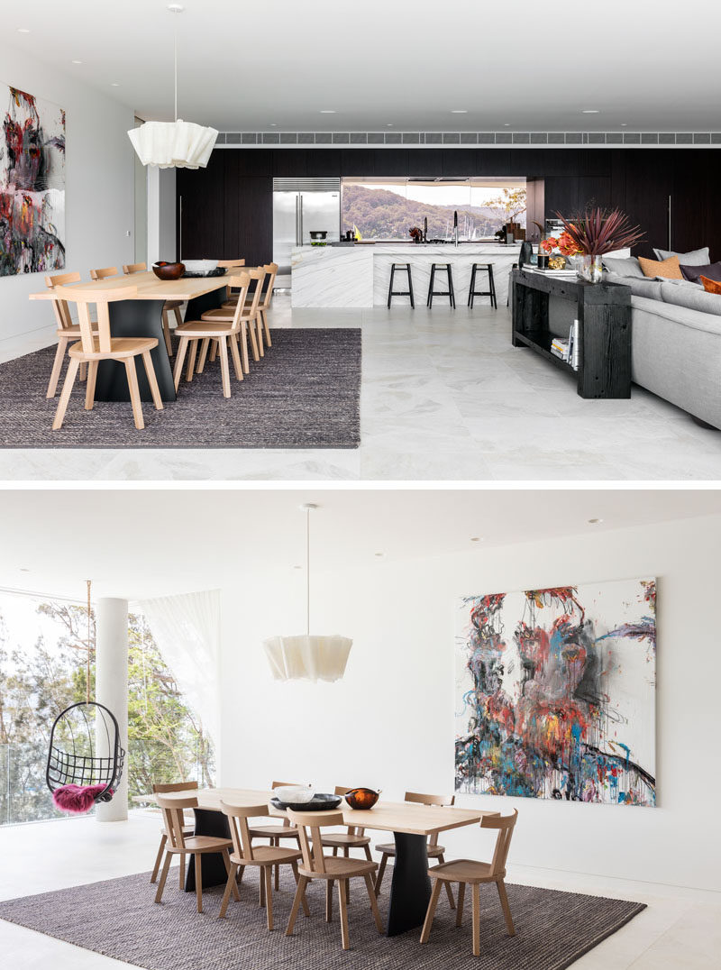 In this open plan interior space, the dining table is anchored by a large rug and single pendant light. #DiningRoom #OpenPlan #ModernInteriorDesign