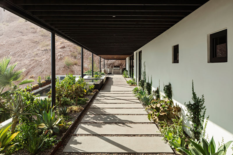 This modern house has a covered patio that's lined with misters to keep the space cool all year round in the desert heat. #Patio #CoveredPatio #Landscaping #Architecture