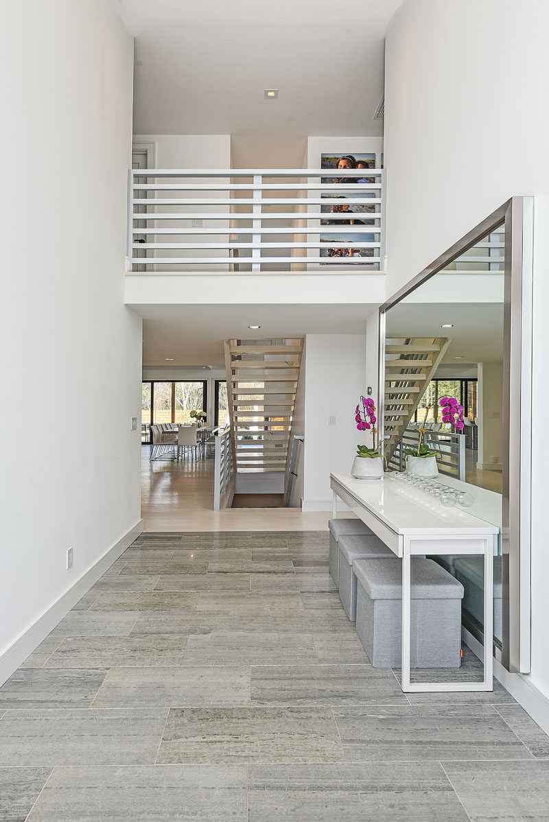 Stepping inside this modern house, the entryway has a high ceiling with tiled flooring and a view of the stairs and upper level. #Entryway #ModernEntryway #InteriorDesign