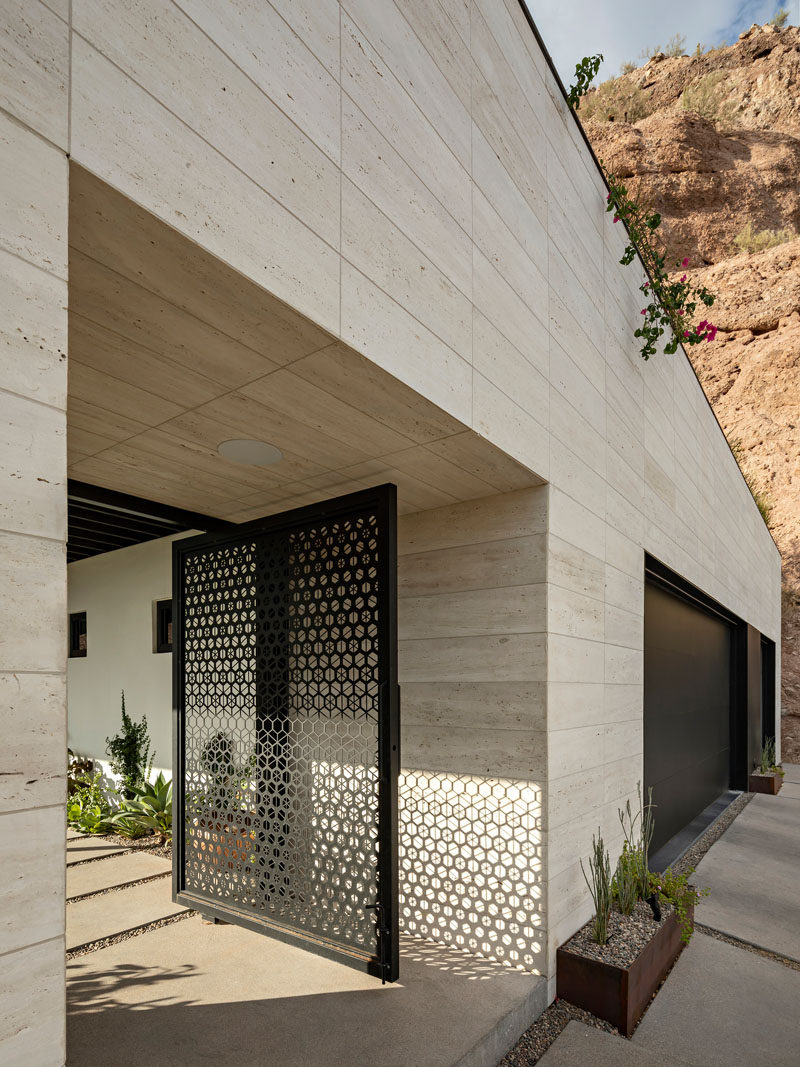 This modern house has a custom pivot gate that features a decorative hexagonal pattern and guides guests to the home. #Gate #EntryGate #ModernGate