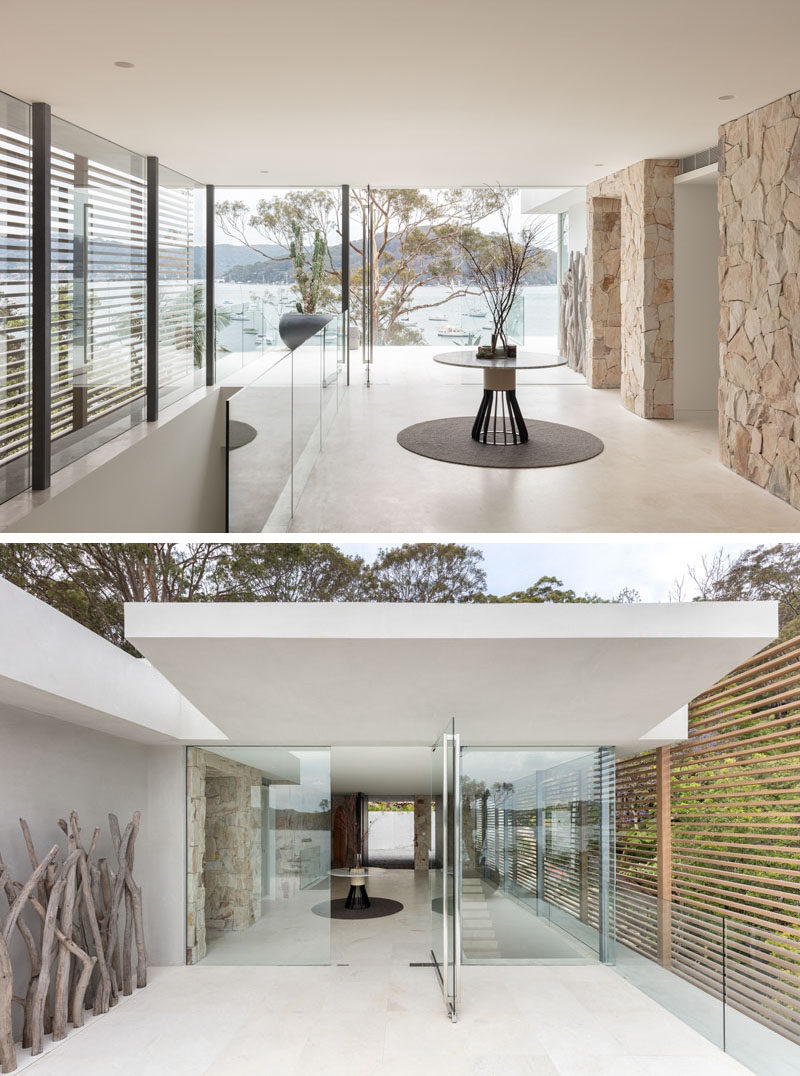 Stepping inside this modern waterfront house, the water views can be appreciated instantly through the floor-to-ceiling windows, while a glass door opens onto a balcony with almost invisible glass railings. #InteriorDesign #Windows #GlassRailings