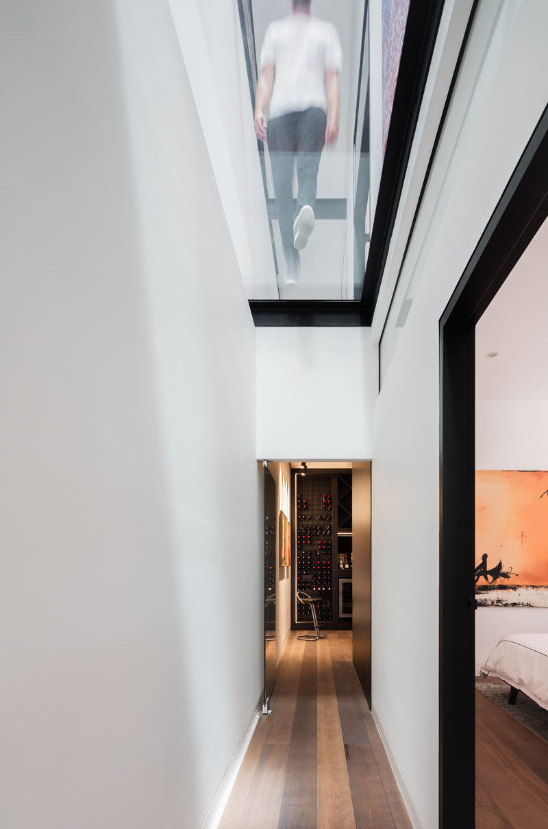 The hallway on the lower level of this modern house takes advantage of the natural light from the skylights and has views of the ridgeline 39 feet (12m) above. #GlassCeiling #GlassFloor #Hallway