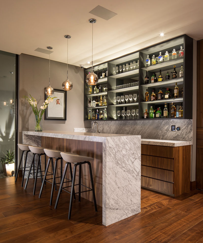 This modern house has a bar that features a shallow shelf with a mirrored back and hidden lighting to highlight the bottles and glassware. #Bar #HomeBar #InteriorDesign