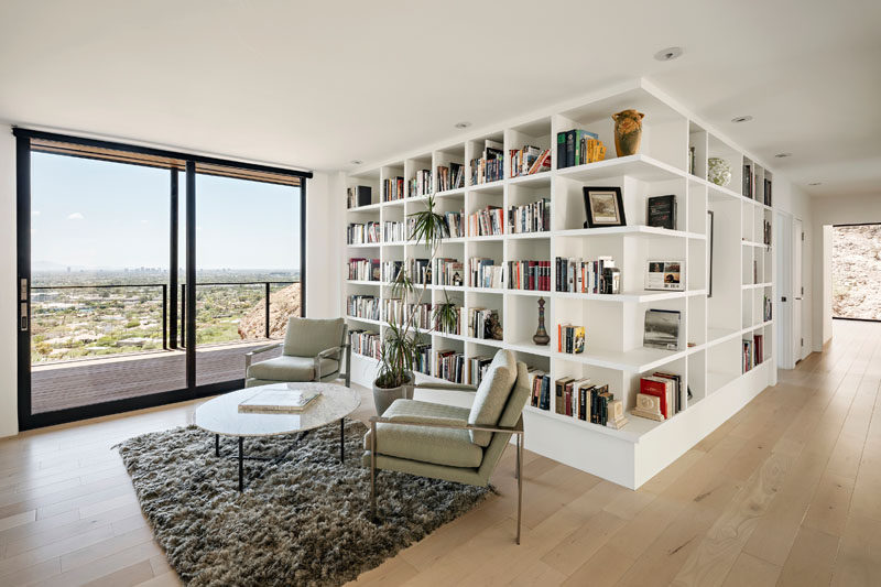 Maple wood floors and white open shelves help to keep this modern home library bright. #Library #Shelving #OpenShelves