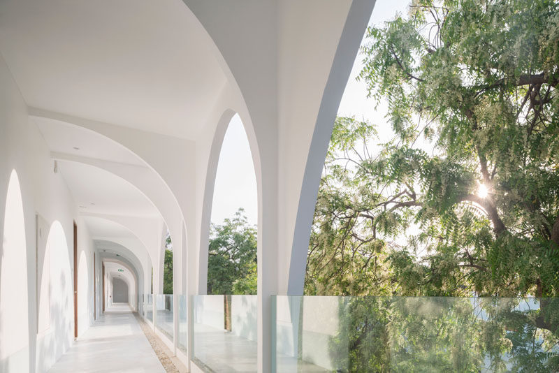 This modern hotel has white arched walkways with glass railings that don't obstruct the view. #HotelDesign #Walkway #GlassRailings