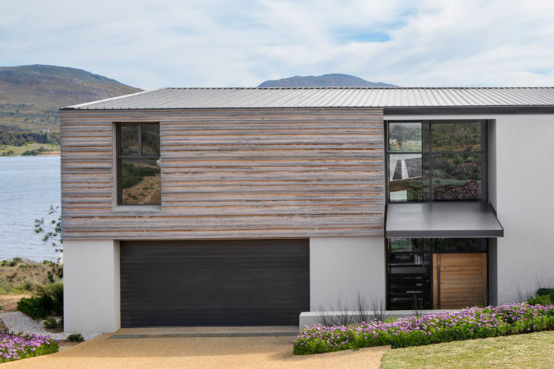 Sections of this modern house are clad in timber, while the roof has been made from corrugated aluminium. The entrance has been designed to be deliberately understated, with a modest canopy sheltering the front door. #ModernHouse #TimberSiding #AluminumRoof