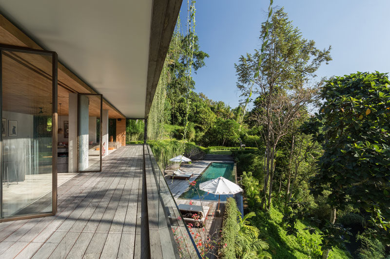 The social areas of this modern house open to a terrace deck that provides anuninterrupted view of the forest, the swimming pool, and the somewhat hidden roof of the building below. #ModernHouse #Deck #SwimmingPool