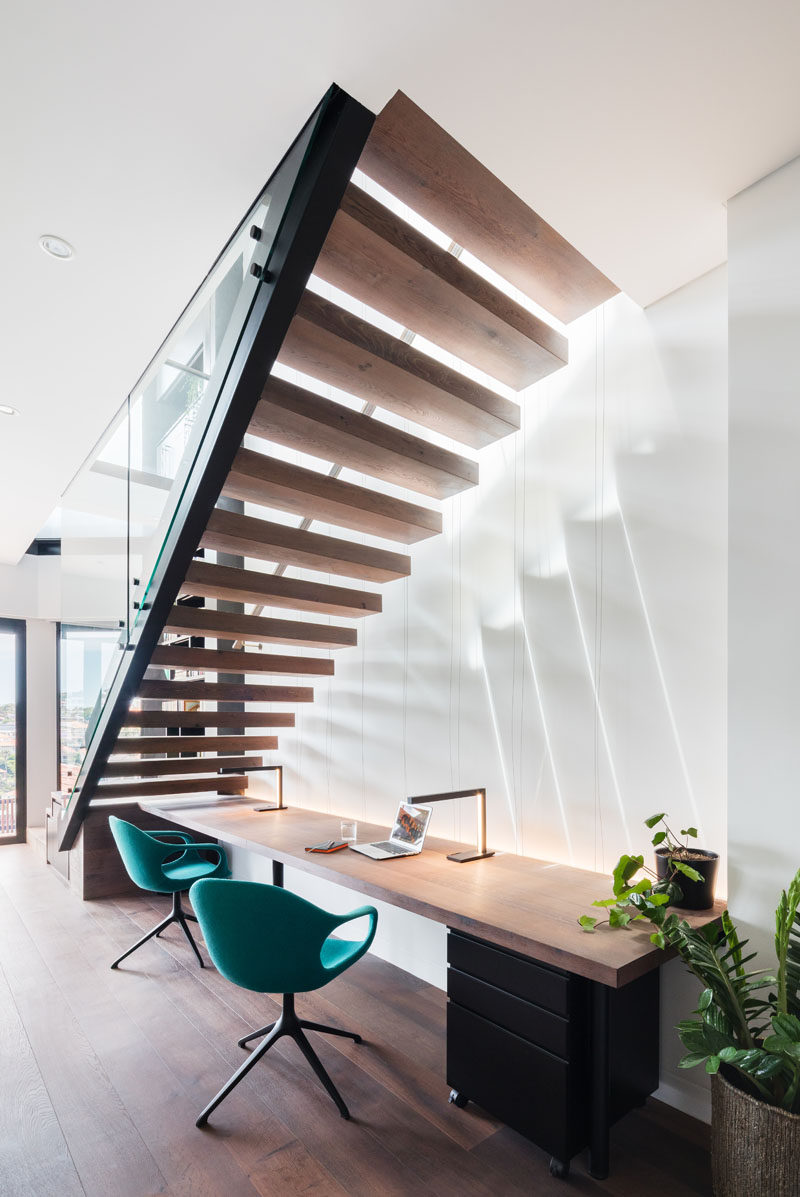 Cantilevering stairs with wood treads and a steel balustrade lead down to the lower level of this modern house. Underneath the stairs is desk with a wood work surface that's large enough for two people. #ModernStairs #CantileveredStairs #HomeOffice