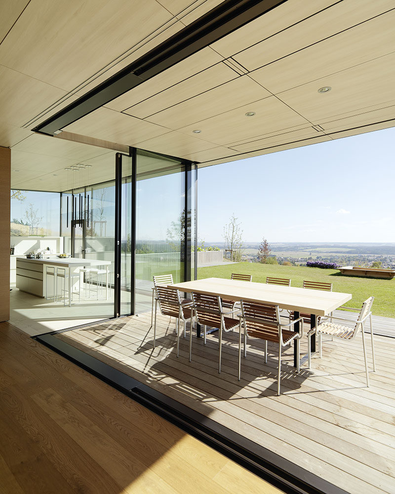 This modern house has an openable glazed corner window arrangement from the kitchen and living space, allows for a semi-outdoor transformation during summer months. #OutdoorDining #GlassWall #IndoorOutdoor