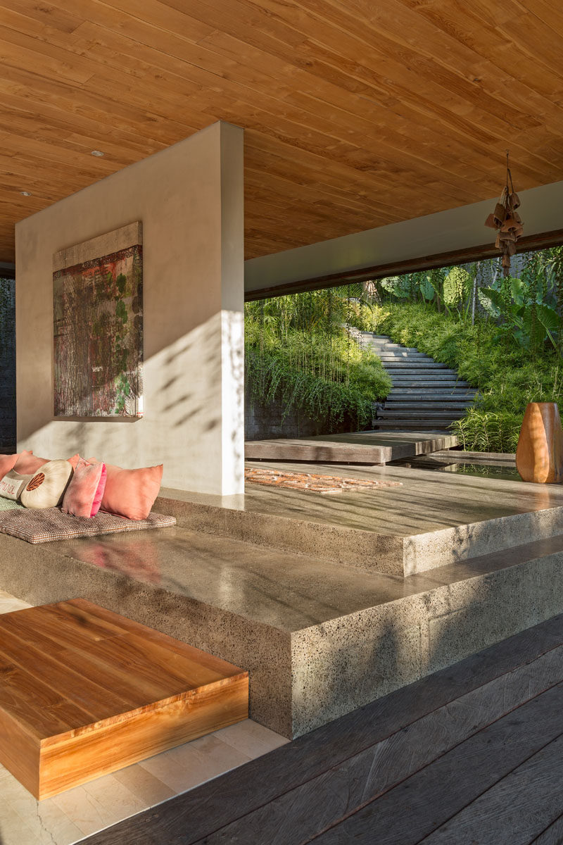 This modern house has a path that leads to the open entrance of the home. Stone, wood and concrete are featured throughout the design of the house. #Architecture #Landscaping