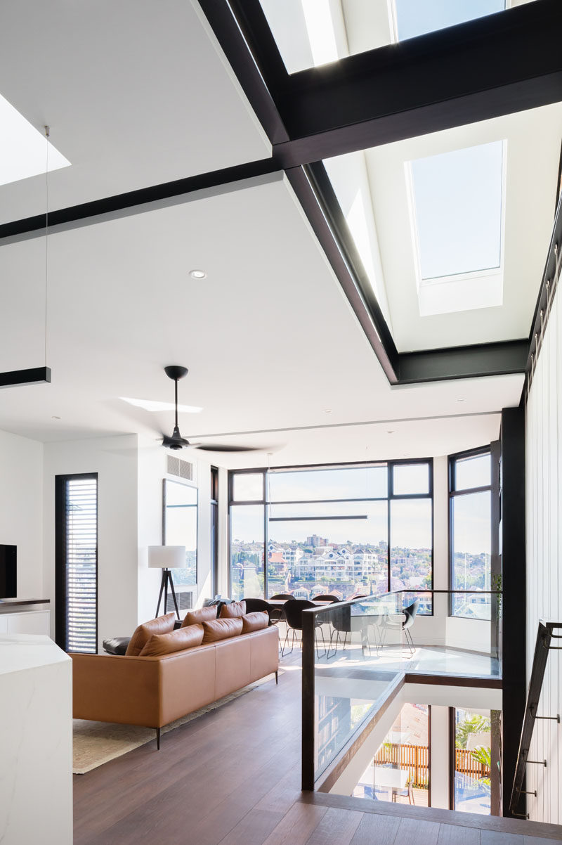 In this modern house, skylights above the stairs filter natural light through to the lower level of the home. #Skylights #ModernInterior #SteelBeams