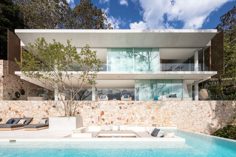This modern house with a swimming pool and sandstone walls, has cantilevered concrete slabs featured as part of the design of the house. #Cantilever #SandstoneWalls #ModernArchitecture #SwimmingPool #SunkenLounge