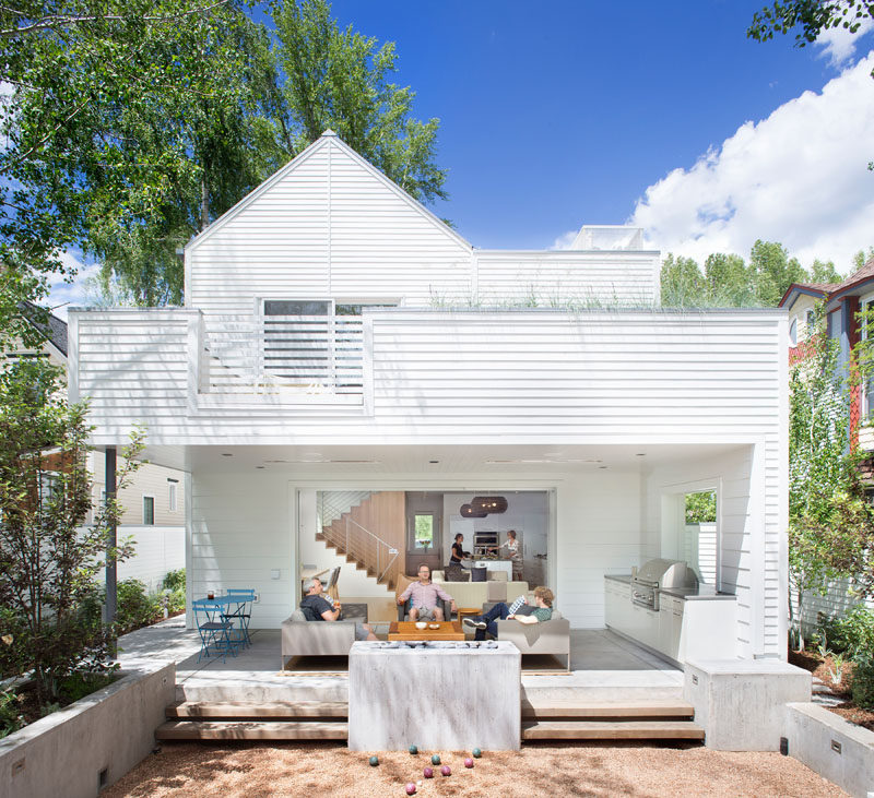This modern house has a covered outdoor area with a lounge, freestanding fireplace, outdoor kitchen, and a bocce court. #OutdoorSpace #OutdoorEntertaining #OutdoorKitchen