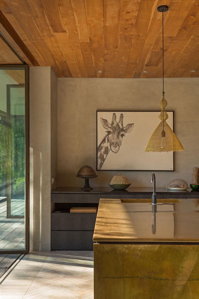 This modern kitchen features a metallic mirrored island and dark wood cabinets. #Kitchen #KitchenDesign #MetallicIsland