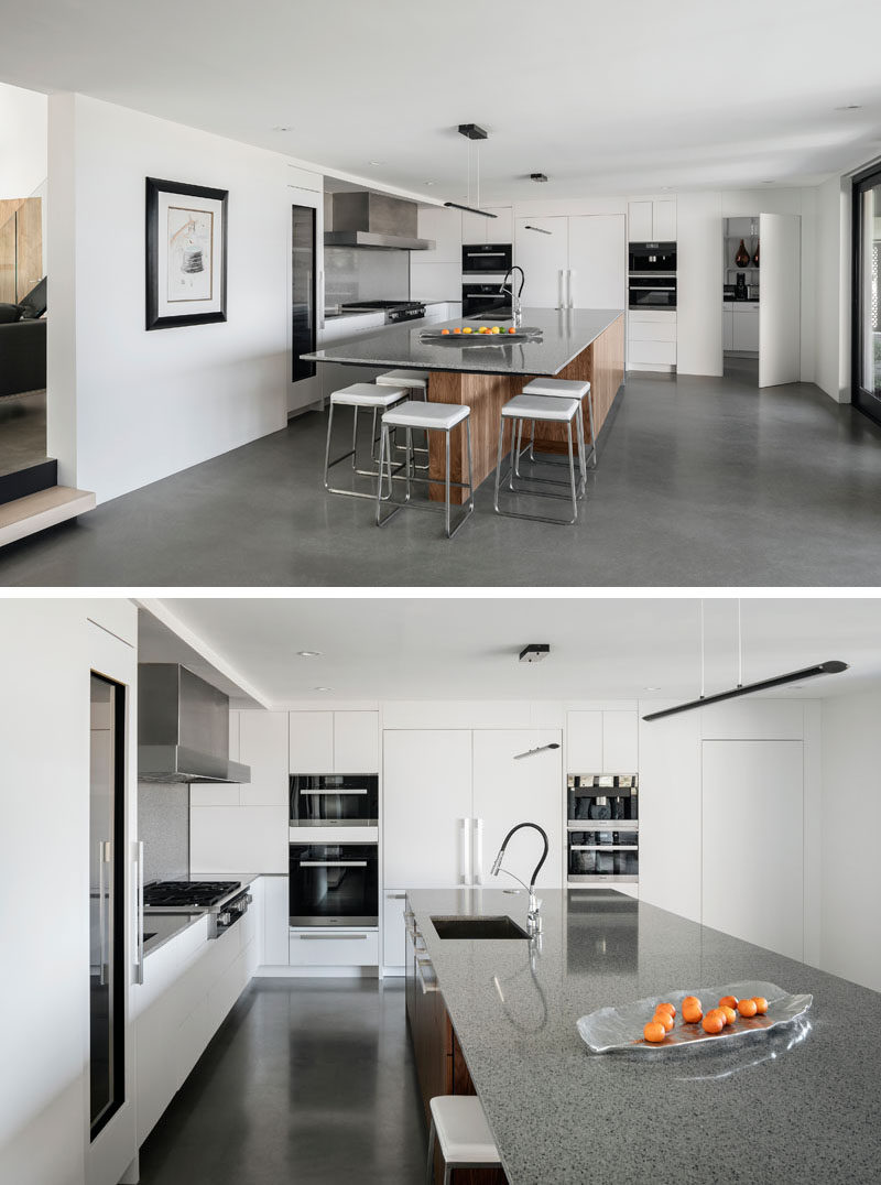 Concrete floors, white and wood cabinets, and quartz counters give this kitchen a modern appearance. #ModernKitchen #KitchenDesign #ConcreteFloors #WhiteKitchen