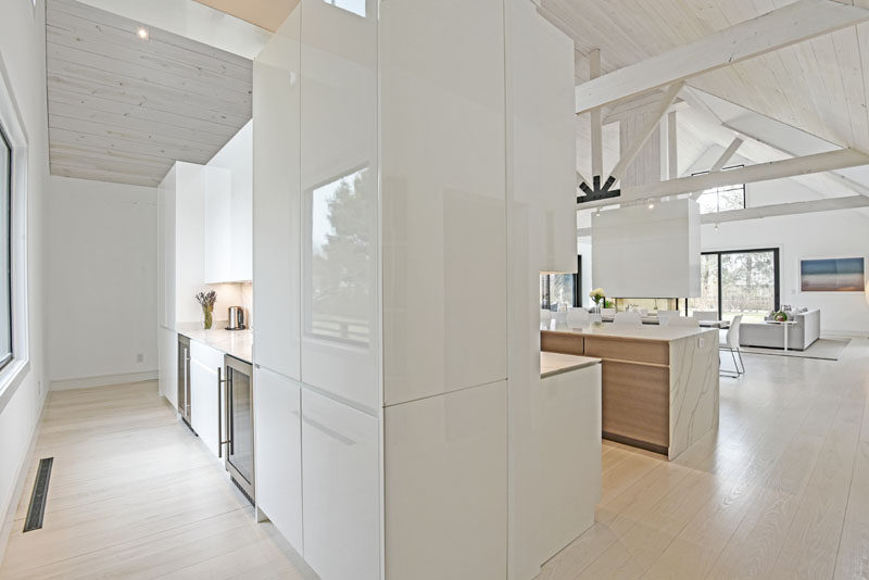 This modern kitchen features a pantry behind it that has views of the garden. #ModernPantry #WhiteCabinets #KitchenDesign