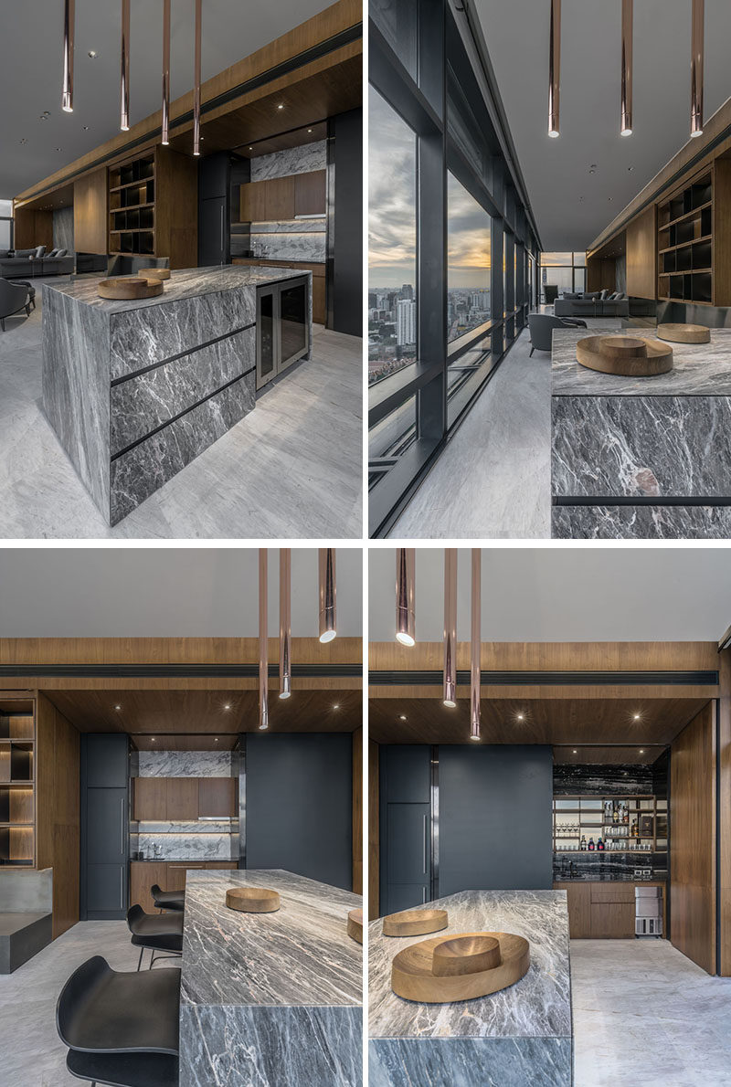 Hidden behind matte black panels in this kitchen area are storage cabinets and a full bar. #Kitchen #Bar #Stone