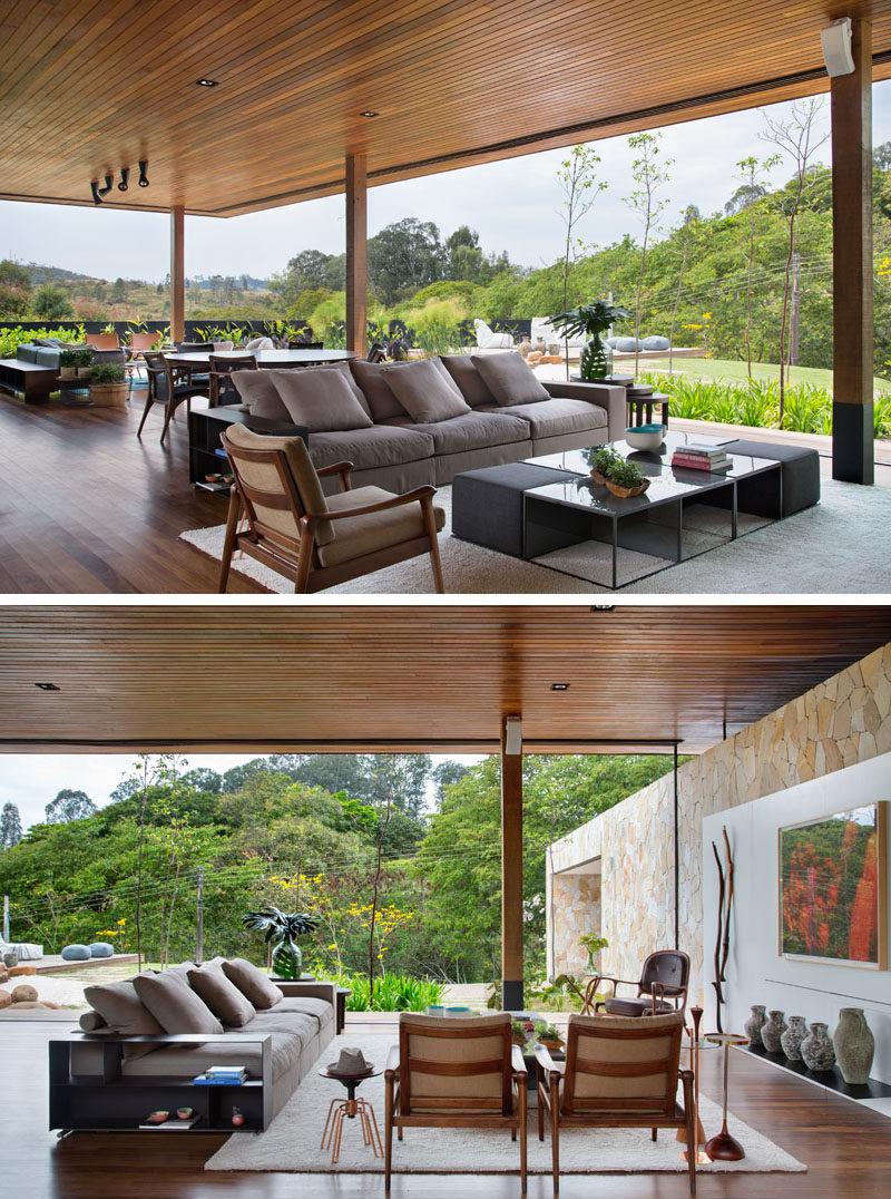 Through the use of sliding glass walls, the designers of the house were able to bring nature to the living areas. The open plan room has a multiple seating area, a dining area, and a kitchen. #IndoorOutdoor #WoodCeiling #Architecture #LivingRoom