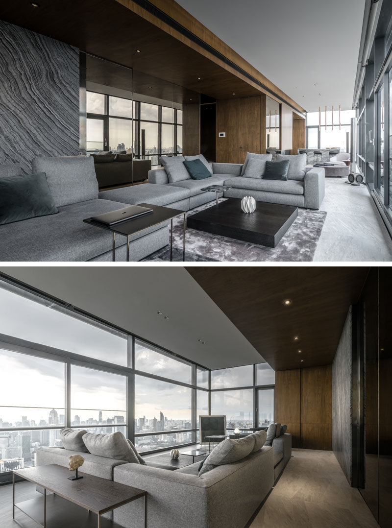 In the living room, a mirrored wall reflects the view, while marble has been used to create an accent wall that complements the kitchen at the opposite end of the room. #LivingRoom #Windows #InteriorDesign #ModernInterior