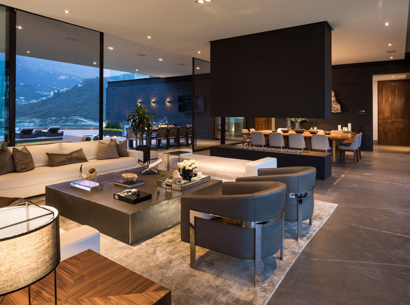 Large sliding glass doors open to connect the exterior and interiors spaces of this modern house, with the living room separated from the dining room by an open fireplace. #Fireplace #LivingRoom #InteriorDesign